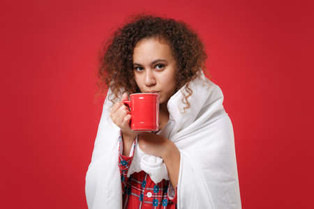 Young african american girl in pajamas homewear posing resting at home isolated on red background. Relax good mood lifestyle concept. Mock up copy space. Wrapping in blanket hold cup of coffee or tea.