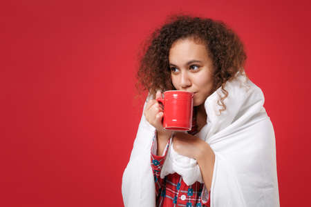 Pretty young african american girl in pajamas homewear resting at home isolated on red background. Relax good mood lifestyle concept. Mock up copy space. Wrapping in blanket hold cup of coffee or tea. Imagens