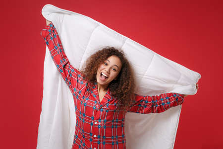 Excited cheerful young african american girl in pajamas homewear posing while resting at home isolated on red background in studio. Relax good mood lifestyle concept. Mock up copy space. Hold blanket. Imagens