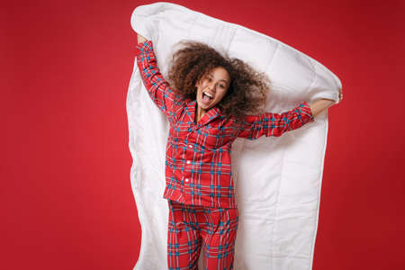 Funny young african american girl in pajamas homewear posing while resting at home isolated on red background. Relax good mood lifestyle concept. Mock up copy space. Jumping with blanket, having fun.