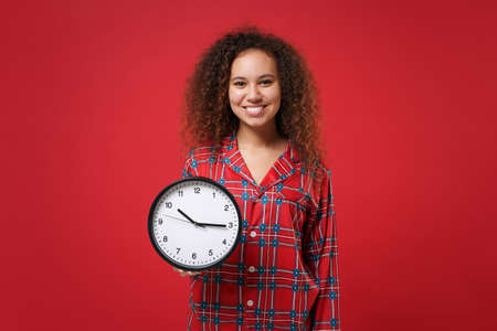 Smiling young african american girl in pajamas homewear posing while resting at home isolated on red wall background studio portrait. Relax good mood lifestyle concept. Mock up copy space. Hold clock. Zdjęcie Seryjne