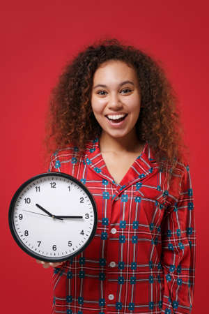 Cheerful young african american girl in pajamas homewear posing while resting at home isolated on red background studio portrait. Relax good mood lifestyle concept. Mock up copy space. Hold clock.