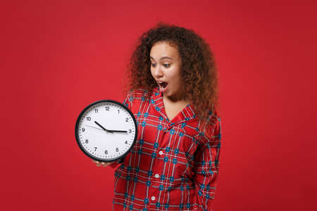 Shocked young african american girl in pajamas homewear posing while resting at home isolated on red wall background studio portrait. Relax good mood lifestyle concept. Mock up copy space. Hold clock. Zdjęcie Seryjne