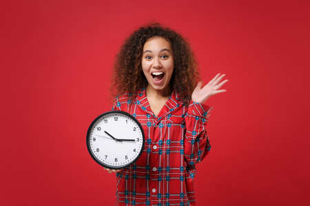 Surprised young african american girl in pajamas homewear posing while resting at home isolated on red background. Relax good mood lifestyle concept. Mock up copy space. Hold clock, spreading hands.