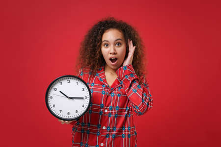 Shocked young african american girl in pajamas homewear posing while resting at home isolated on red background. Relax good mood lifestyle concept. Mock up copy space. Hold clock put hand on cheek.