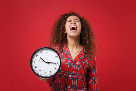 Frustrated young african american girl in pajamas homewear posing while resting at home isolated on red wall background. Relax good mood lifestyle concept. Mock up copy space. Hold clock screaming.