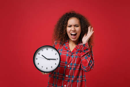 Dissatisfied young african american girl in pajamas homewear posing while resting at home isolated on red wall background. Relax good mood lifestyle concept. Mock up copy space. Hold clock screaming.
