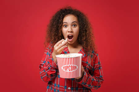 Shocked young african american girl in pajamas homewear posing while resting at home isolated on red wall background. Relax good mood lifestyle concept. Mock up copy space. Hold bucket of popcorn.