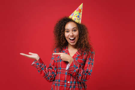 Excited young african american girl in pajamas homewear, birthday hat resting at home isolated on red background. Relax good mood lifestyle concept. Mock up copy space. Point hand, index finger aside.