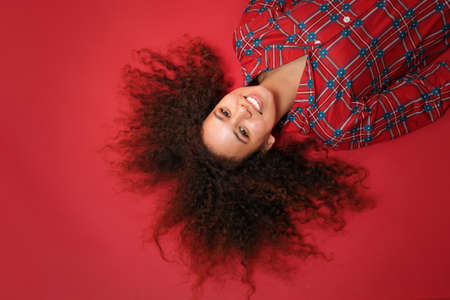 Overhead top view of smiling young african american girl in pajamas homewear resting at home isolated on red background. Relax good mood lifestyle concept. Mock up copy space. Lying, looking camera.