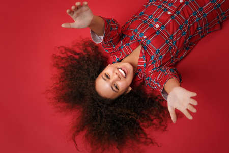 Overhead top view of cheerful young african american girl in pajamas homewear posing resting at home isolated on red wall background. Relax good mood lifestyle concept. Lying with outstretched hands.