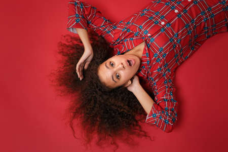 Overhead top view of shocked young african american girl in pajamas homewear posing resting at home isolated on red background in studio. Relax good mood lifestyle concept. Lying, keeping mouth open.