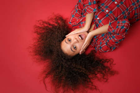 Overhead top view of shocked young african american girl in pajamas homewear rest at home isolated on red background. Relax good mood lifestyle concept. Lying, keeping mouth open, put hands on cheeks.