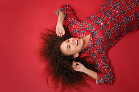 Overhead top view of laughing african american girl in pajamas homewear rest at home isolated on red background. Relax good mood lifestyle concept. Lying, keeping eyes closed, rising stretching hands.