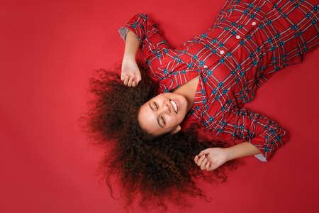 Overhead top view of cheerful african american girl in pajamas homewear rest at home isolated on red background. Relax good mood lifestyle concept. Lying, keeping eyes closed, rising stretching hands. 写真素材