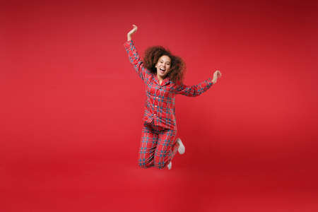 Laughing young african american girl in pajamas homewear birthday hat posing resting at home isolated on red background. Relax good mood lifestyle concept. Mock up copy space. Jumping spreading hands.