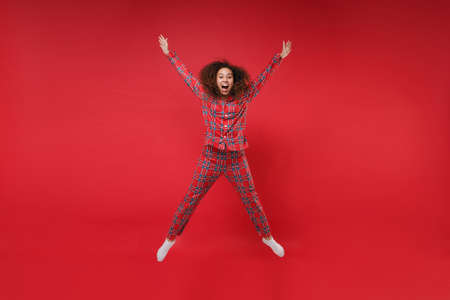 Excited young african american girl in pajamas homewear birthday hat resting at home isolated on red background. Relax good mood lifestyle concept. Mock up copy space. Jumping spreading hands, legs. 写真素材