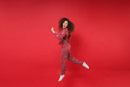 Side view of funny young african american girl in pajamas homewear birthday hat resting at home isolated on red background. Relax good mood lifestyle concept. Mock up copy space. Jumping like running. 写真素材