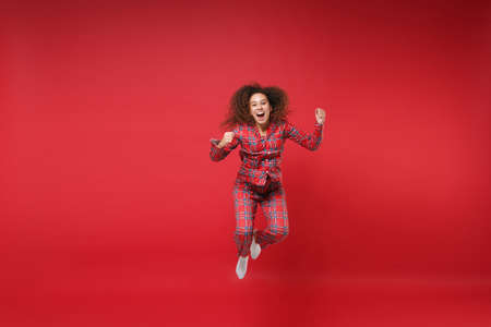 Joyful young african american girl in pajamas homewear birthday hat resting at home isolated on red background. Relax good mood lifestyle concept. Mock up copy space. Jumping doing winner gesture. 写真素材