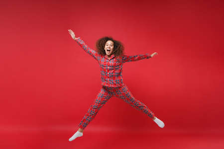 Crazy young african american girl in pajamas homewear birthday hat resting at home isolated on red background. Relax good mood lifestyle concept. Mock up copy space. Jumping spreading hands, legs.