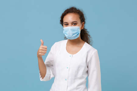 African american doctor woman isolated on blue background. Female doctor in white medical gown, sterile face mask showing thumb up. Healthcare personnel health medicine concept. Mock up copy space. 写真素材
