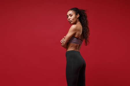 Side view of young african american sports fitness woman in sportswear posing working out isolated on red background. Sport exercises healthy lifestyle concept. Holding hands crossed, looking camera 写真素材