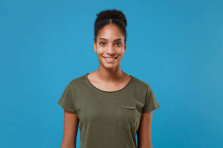 Smiling young african american woman girl in casual t-shirt posing isolated on bright blue background studio portrait. People sincere emotions lifestyle concept. Mock up copy space. Looking camera 写真素材