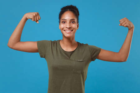 Smiling young african american woman girl in casual t-shirt posing isolated on blue background studio portrait. People sincere emotions lifestyle concept. Mock up copy space. Showing biceps, muscles. Imagens