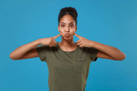 Young african american woman girl in casual t-shirt posing isolated on blue background studio portrait. People emotion lifestyle concept. Mock up copy space. Pointing index fingers on blowing cheeks.