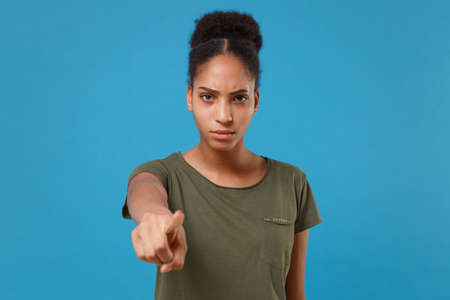 Strict young african american woman girl in casual t-shirt posing isolated on bright blue background studio portrait. People lifestyle concept. Mock up copy space. Pointing index finger on camera.