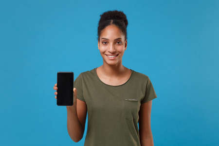 Smiling young african american woman girl in casual t-shirt posing isolated on blue background studio portrait. People lifestyle concept. Mock up copy space. Hold mobile phone with blank empty screen.