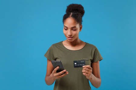 Young african american woman girl in casual t-shirt posing isolated on bright blue wall background studio portrait. People lifestyle concept. Mock up copy space. Using mobile phone credit bank card.