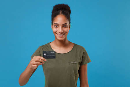 Smiling young african american woman girl in casual t-shirt posing isolated on bright blue background studio portrait. People emotions lifestyle concept. Mock up copy space. Hold credit bank card. Reklamní fotografie