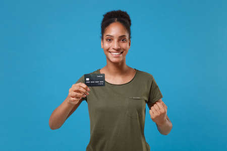 Joyful young african american woman girl in casual t-shirt posing isolated on blue wall background in studio. People lifestyle concept. Mock up copy space. Hold credit bank card, doing winner gesture. Reklamní fotografie