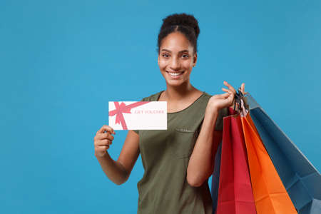 Joyful young african american woman girl in casual t-shirt isolated on blue background. People lifestyle concept. Mock up copy space. Hold package bag with purchases after shopping, gift certificate.
