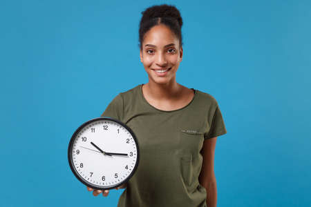 Smiling young african american woman girl in casual t-shirt posing isolated on bright blue wall background studio portrait. People sincere emotions lifestyle concept. Mock up copy space. Hold clock.