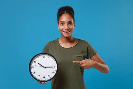 Funny young african american woman girl in casual t-shirt posing isolated on bright blue wall background studio portrait. People lifestyle concept. Mock up copy space. Pointing index finger on clock.