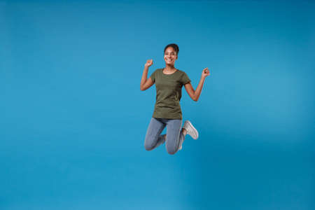 Smiling young african american woman girl in casual clothes posing isolated on bright blue background studio portrait. People emotions lifestyle concept. Mock up copy space. Jumping, clenching fists.