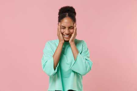 Smiling young african american woman girl in green sweatshirt posing isolated on pastel pink wall background. People lifestyle concept. Mock up copy space. Keeping eyes closed, put hands on cheeks.