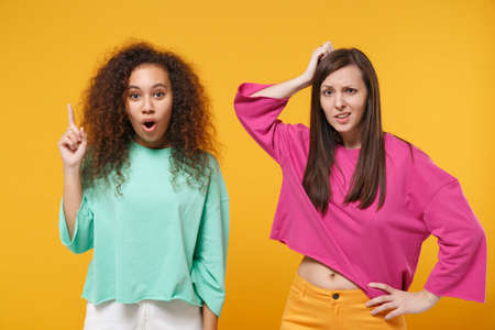 Two women friends european african american in pink green clothes isolated on yellow background. People lifestyle concept. Mock up copy space. Holding index finger up with great idea put hand on head.