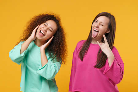 Two women friends european african girls in pink green clothes posing isolated on yellow background. People lifestyle concept. Mock up copy space. Cover ears with hands, showing heavy metal rock sign.