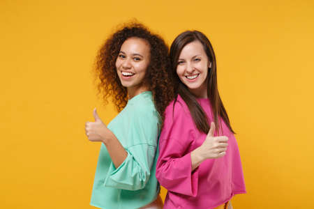 Two cheerful women friends european and african american girls in pink green clothes posing isolated on yellow orange wall background. People lifestyle concept. Mock up copy space. Showing thumbs up.