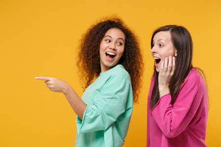 Two amazed women friends european and african american girls in pink green clothes posing isolated on yellow wall background. People lifestyle concept. Mock up copy space. Pointing index finger aside.