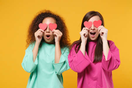 Two excited women friends european african american in pink green clothes posing isolated on yellow wall background. People lifestyle concept. Mock up copy space. Covering eyes with little red hearts.