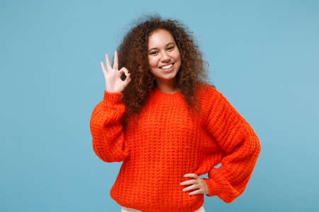 Smiling young african american girl in casual orange knitted clothes isolated on pastel blue background studio portrait. People sincere emotions, lifestyle concept. Mock up copy space. Looking camera 写真素材