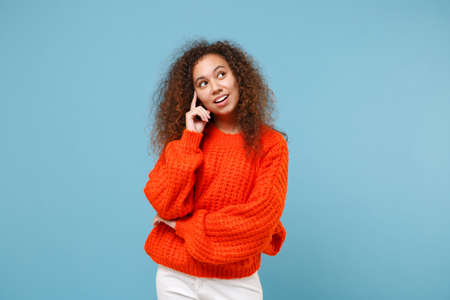 Smiling young african american girl in casual orange knitted clothes isolated on pastel blue background studio portrait. People sincere emotions, lifestyle concept. Mock up copy space. Looking aside