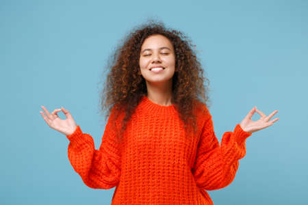 Young african american girl in casual orange clothes hold hands in yoga gesture, relaxing meditating isolated on pastel blue background studio portrait. People lifestyle concept. Mock up copy space