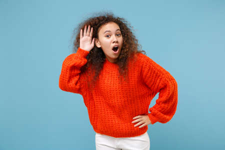 Amazed young african american girl in casual orange knitted clothes isolated on pastel blue background studio portrait. People lifestyle concept. Mock up copy space Try to hear you with hand near ear 写真素材