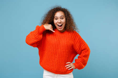 Excited young african american girl in casual orange knitted clothes isolated on pastel blue background in studio. People lifestyle concept. Mock up copy space. Doing phone gesture says call me back. Stock fotó