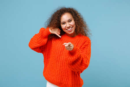 Smiling african american girl in orange knitted clothes isolated on pastel blue background. People lifestyle concept. Mock up copy space. Doing phone gesture says call me back point finger on camera.